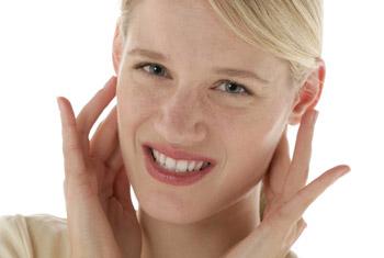 Kopfschmerz, Verspannung. Eine Frau greift sich an ihren Kiefer und hat ein schmerzverzerrtes Gesicht.