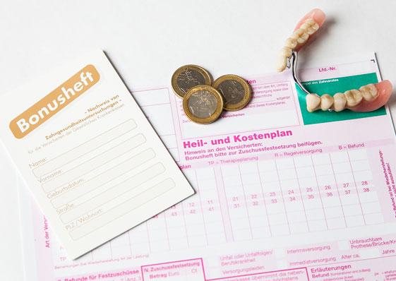 Bonusheft, ein paar Euro-Münzen, ein Heil- und Kostenplan sowie eine Teilprothese liegen auf einem Tisch