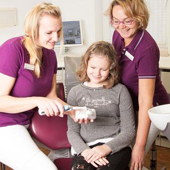 2 Zahnarzt-Assistentinnen üben mit einem Kind das Zähneputzen
