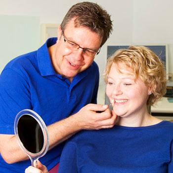 Zahnarzt vergleicht mit einem Patient dessen Zahnfarbe mit dem Zahnersatz