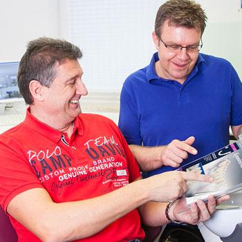 Zahnarzt berät einen älteren Mann zum Thema Zahnersatz und zeigt ihm Bilder in einer Broschüre