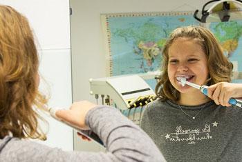 Mädchen putzt seine Zähne, man sieht sie gleichzeitig schräg von hinten und in einem Spiegel
