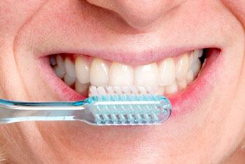 Frau mit strahlend weißen Zähnen putzt ihre Zähne mit einer Zahnbürste
