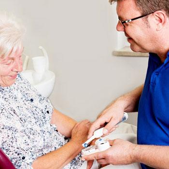 Zahnarzt erklärt einer älteren Patientin den Umgang mit einer elektrischen Zahnbürste