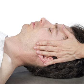 Bei einer Untersuchung wird einem liegenden Patienten der Kiefer und die Kaumuskulatur abgetastet