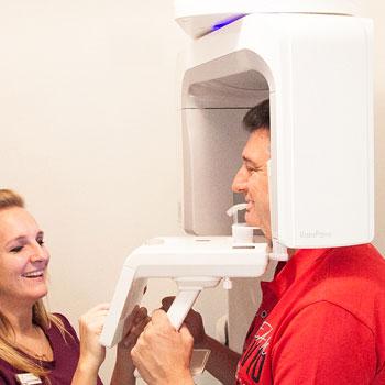 Eine Zahnarzt-Assistentin führt eine digitale Röntgenaufnahme an einem Patienten durch
