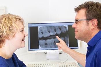 Zahnarzt und Patientin betrachten ein digitales Röntgenbild am Monitor