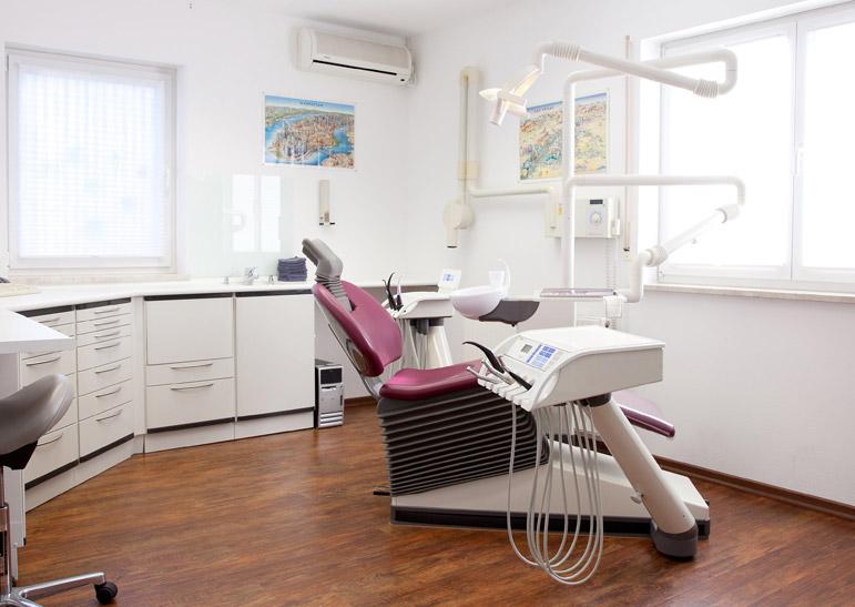 Geräumiger, heller Raum mit einem bordeaux-farbenem Behandlungsstuhl.