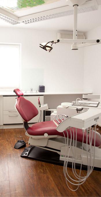 Geräumiger, heller Raum mit einem bordeaux-farbenem Behandlungsstuhl, Plakat an der Decke zur Ablenkung für Kinder.
