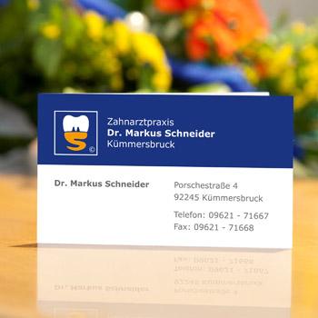 """Visitenkarte """"Dr. Markus Schneider"""" in Blau und Weiß ist auf der Rezeptionstheke aufgestellt"""