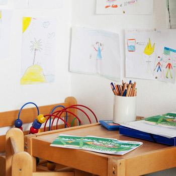 Kinderspielecke mit kleinem Tisch und Stühlen, Spielsachen und gemalten Bildern an der Wand