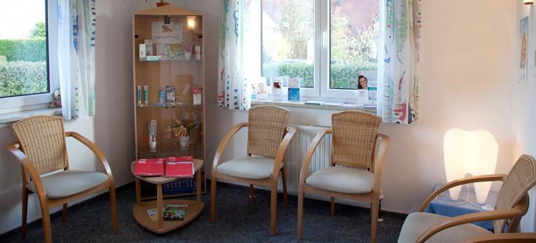 Freundliches Wartezimmer mit Korb-Armlehnstühlen, im Eck steht eine Glasvitrine